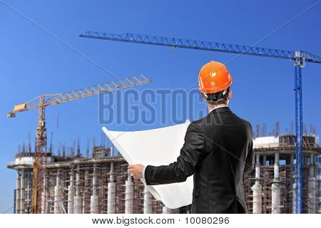 Foreman Holding A Blueprints And Looking Towards The Construction Site