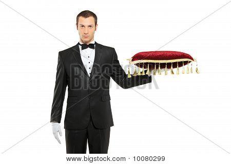 Mann In einem schwarzen Anzug mit einen Kissen