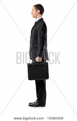 Full Length Portrait Of A Businessman Holding A Leather Briefcase