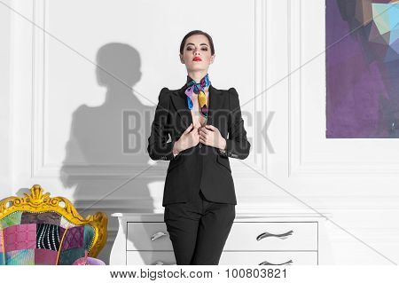 Female Fashion Model In Suit Staying In White Minimalistic Art Interior