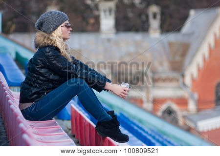 Young woman sit with cup coffee outdoor.