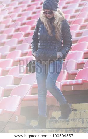 Young woman down the stairs of the stadium.