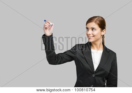 Beautiful businesswoman drawing on a glass board with a marker