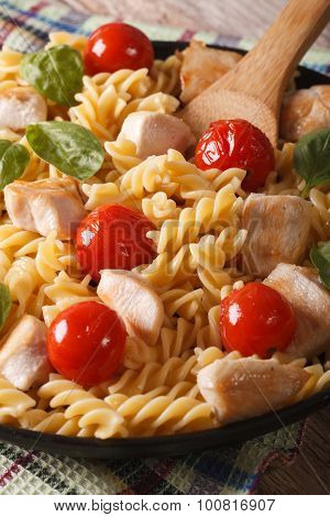 Pasta With Chicken, Tomato And Basil Close-up On A Plate. Vertical
