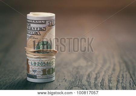 hundred dollar bills on wood table