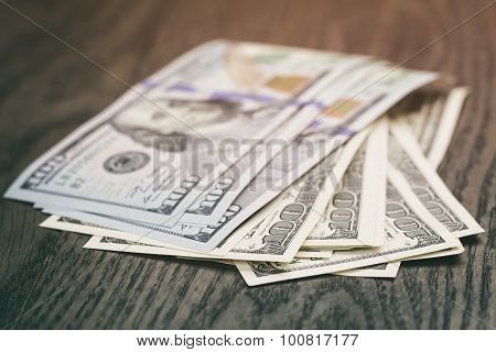 hundred dollar bills on wood table
