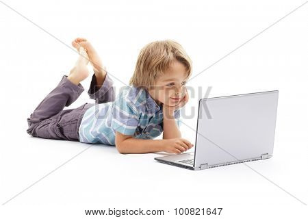 Boy playing on a laptop computer concept for child internet safety, social media or education and homework
