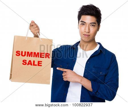 Asian mixed Indian man finger point to shopping bag for showing phrase of summer sale