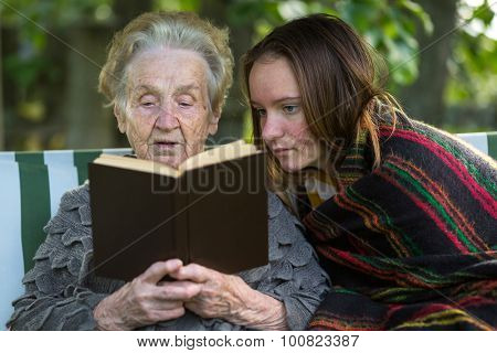 An elderly woman reading a book sitting in the garden with his granddaughter.