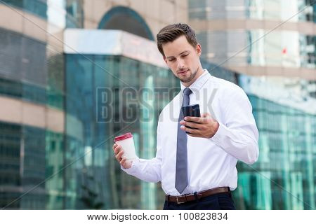 Young Businessman read on the cellphone and hold with coffee cup