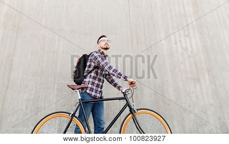 people, travel, tourism, leisure and lifestyle - happy young hipster man with fixed gear bike and backpack on city street