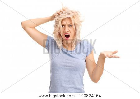 Confused girl with messy hair gesturing with her hand and looking at the camera isolated on white background