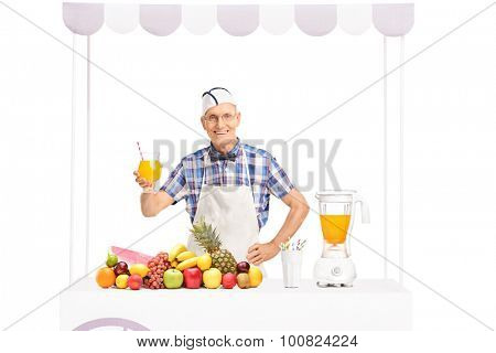 Mature soda jerk posing behind a stand full of fresh fruits and holding a glass of orange juice isolated on white background