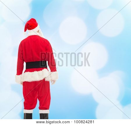 christmas, holidays and people concept - man in costume of santa claus from back over blue lights background