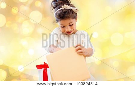 holidays, christmas, birthday childhood and people concept - smiling little girl with gift box over yellow lights background