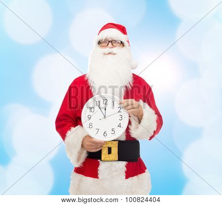 christmas, holidays and people concept - man in costume of santa claus with clock showing twelve pointing finger over blue lights background