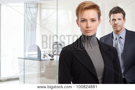 Closeup portrait of attractive young businesswoman and male colleague at bright office.
