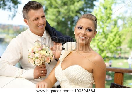 Happy young couple on wedding-day smiling outdoors.