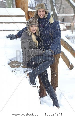 Outdoor photo of happy loving couple smiling at winter in snowfall.