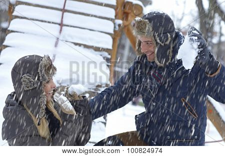Young loving couple having fun, throwing snowball, laughing.