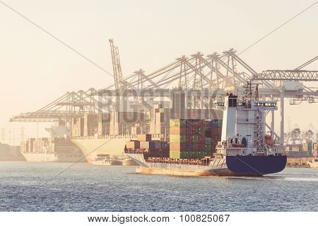 Huge container ship, coasters, supply vessels being loaded and unloaded by the huge overhead cranes of a busy transhipment harbor during a hazy afternoon