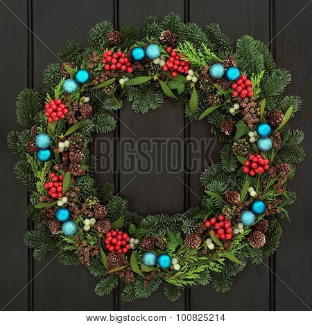 Christmas wreath with blue bauble decorations, holly, mistletoe, pine cones and blue spruce fir over dark blue oak front door background.