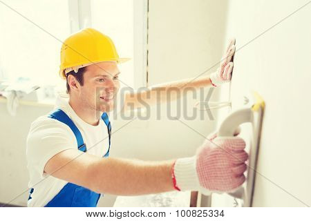 business, building, profession and people concept - smiling builder with grinding tool indoors