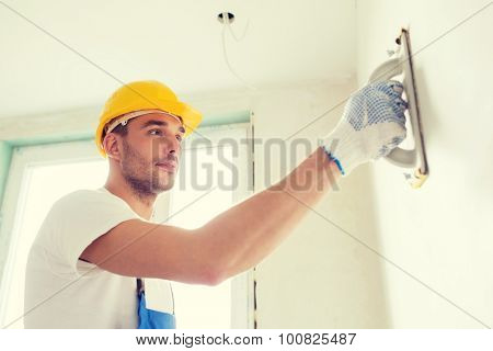 building, profession and people concept - builder in hardhat sanding wall indoors