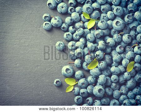Blueberries vintage style over dark background. Blueberry close up. Ripe and tasty blueberries with green leaves border design. Diet concept. Space for your text