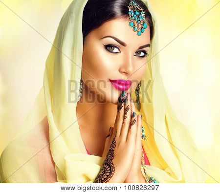 Beauty Indian girl with mehndi tattoos hold palms together. Beautiful Hindu exotic woman in sari and emerald oriental jewels looking in camera. India. Traditions concept