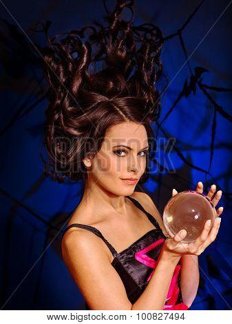 Young woman  with crystal ball. Fashion Halloween.