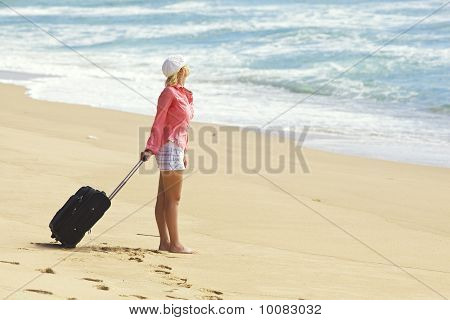 Young Woman With Suitcase On The Beach