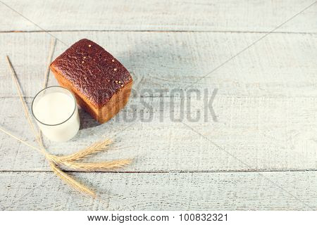 Bread With Spikelets Of Wheat And Glass Of Milk On A Boards.