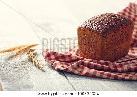 Bread On A Cloth With Spikelets Of Wheat On A Wooden Boards