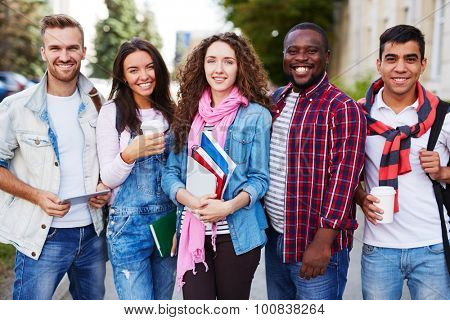 Friendly students in casualwear looking at camera outdoors