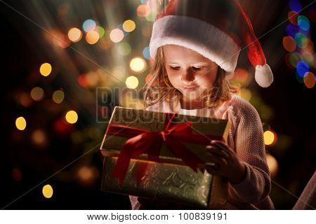 Pretty girl in Santa cap looking into open magic giftbox