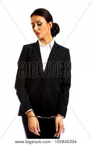 Worried beautiful businesswoman with handcuffs.