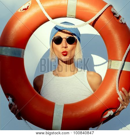 Funny Fashion Blonde On Wall Background With Orange Lifebuoy