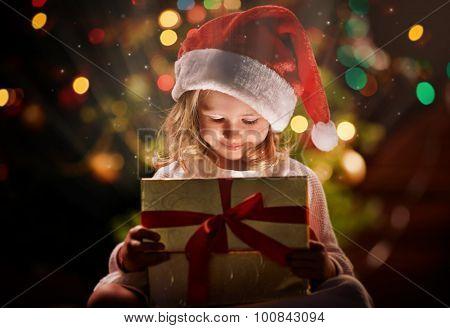 Happy girl in Santa cap looking at magic gift in box on xmas night
