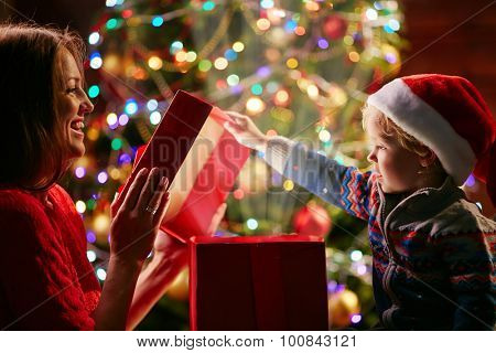 Little boy in Santa cap opening magic giftbox with his mother near by