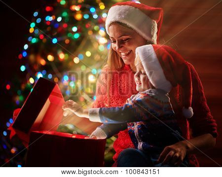 Happy woman and her son admiring xmas present in red giftbox