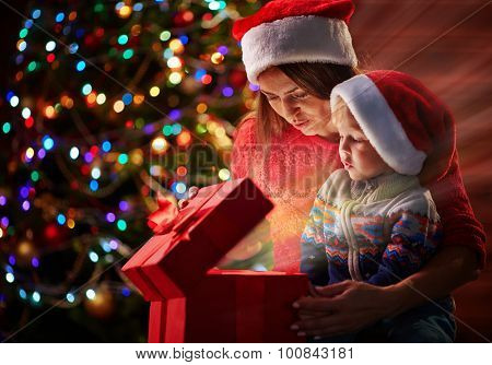 Cute boy and his mother in Santa caps looking at light in giftbox