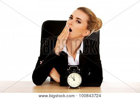 Yawning businesswoman behind the desk.