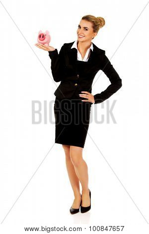 Young businesswoman saving money in piggybank.