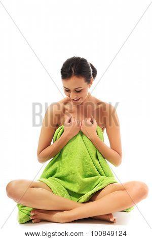 Spa woman wrapped in towel sitting cross legged.