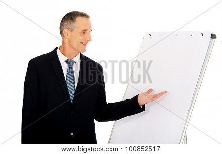 Mature businessman presenting something on flip chart.