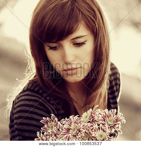 Sad young woman with a flowers outdoor