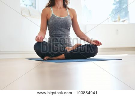 Woman Doing Padmasana Yoga On The Floor