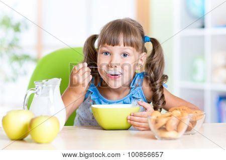 cute little girl eating cereal with milk in nursery