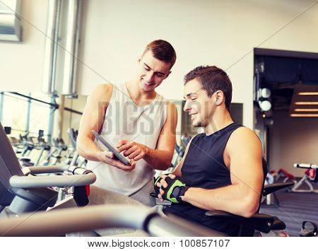 sport, fitness, equipment, technology and people concept - men with tablet pc computer exercising on gym machine